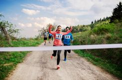 Large group of people running a race competition in nature. A large group of active people running a race competition in nature stock photo