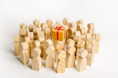 A large group of people surrounds a box with a present. The concept of choosing a good gift, limited number, all sold out. A gift stock photo
