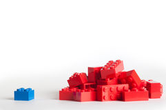 A large group of red lego blocks and one blue Stock Photos