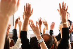 Large group of seminar audience in class room. Raised hands and arms of large group of people in class room, audience voting in professional education Royalty Free Stock Image