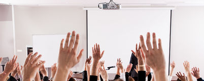 Large group of seminar audience in class room. Raised hands and arms of large group of people in class room, audience voting in professional education Royalty Free Stock Photography