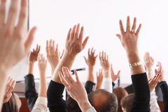 Large group of seminar audience in class room. Raised hands and arms of large group of people in class room, audience voting in professional education Stock Photo