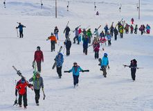Large group of skiers returnig from ski slopes in a mountain resort in winter. Large group of skiers on ski slopes in a mountain resort in winter in Madaras Stock Image