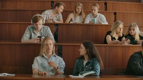 A large group of students during the break communicate with each other in the classroom. Large class.  stock video
