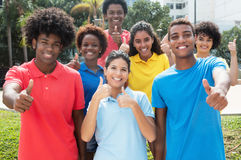 Large group of successful international young adults showing thu royalty free stock photo