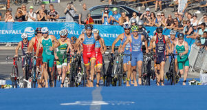 Large group of triathletes running in the transition zone Stock Photo