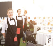 A large group of waiters and waitresses next to served tables Royalty Free Stock Photography