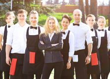 A large group of waiters and waitresses in the open air stand one after another Stock Photos