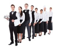 Large group of waiters and waitresses standing in row. Isolated on white Stock Photo