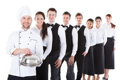 Large group of waiters and waitresses standing in row. Isolated on white Royalty Free Stock Image