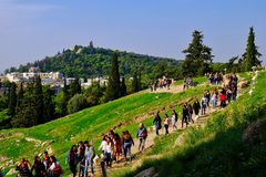 Large Guided Tour Group, Acropolis Slopes, Athens, Greece. A large guided tour group walking along a path on the Acropolis Slopes archeological site, Athens stock image