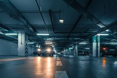 Large hall with columns of underground car parking garage with many automobiles in modern mall or shopping center inside Royalty Free Stock Images