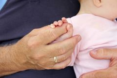 The Large Hand of a Man Holding the Tiny Fingers of a Baby Girl. A large hand of a grandfather or father is holding the tiny fingers of a little baby girl as she Stock Photo