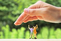 Large hand protecting two very small children. Large hand building a protective roof over two minature children standing in front of a green landscape stock photography