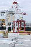Large harbor crane loading containers. On a a large cargo vessel Stock Images