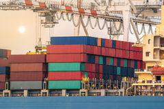 Large harbor cranes loading containers in the ships wiht sunset scene Royalty Free Stock Photo