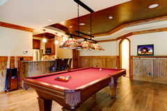 Large hardwood floor room with pool table and bar. Royalty Free Stock Photos