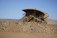 A large haul truck leaving with dirt. Gold mine operation in open gold mine pit with large haul truck leaving with dirt royalty free stock photo
