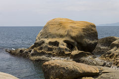 Large head-shaped rock in the seashore of Yehliu Stock Image