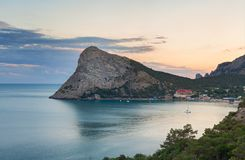 Large headland in the sea near the resort town in the Bay at sunset. Cape Chyken Peninsula of Crimea, resort Noviy Svet Stock Image