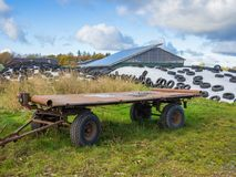 Large heap of silage as animal fodder covered in tires and white plastic and agricultural trailer, farm in North Germany Royalty Free Stock Photo