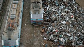 Large heaps of metal scrap and containers with garbage are near a railway with trains in day in cloudy weather,. Large heaps of metal scrap and containers with stock video
