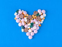 A large heart of colorful pills on a blue background stock photography