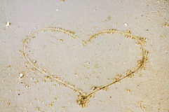 Large heart draw by hand on sand beach for valentine concept Stock Images
