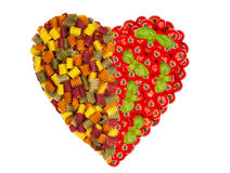 Large heart made of pasta noodles with tomatoes and basil Stock Photos