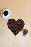 Large heart made of coffee beans, cup of coffee and bulb with coffee beans inside on a light wooden background, top view. Large heart made of coffee beans, cup Stock Image