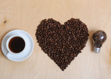 Large heart made of coffee beans, cup of coffee and bulb with coffee beans inside on a light wooden background, top view. Large heart made of coffee beans, cup Stock Photography