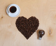 Large heart made of coffee beans, cup of coffee and bulb with coffee beans inside on a light wooden background, top view. Large heart made of coffee beans, cup Royalty Free Stock Photo