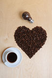 Large heart made of coffee beans, cup of coffee and bulb with coffee beans inside on a light wooden background, top view Stock Images