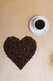 Large heart made of coffee beans and a cup of coffee on a light wooden background, top view Stock Images