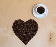 Large heart made of coffee beans and a cup of coffee on a light wooden background, top view Stock Photos