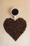 Large heart made of coffee beans and a cup of coffee on a light wooden background, top view Royalty Free Stock Photo