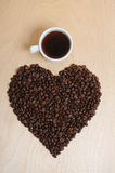 Large heart made of coffee beans and a cup of coffee on a light wooden background, top view Royalty Free Stock Image