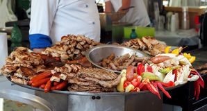 Large heated tray with the traditional serbian street food. The typical grilled meats with vegetables. Large heated tray with the traditional serbian street food stock images