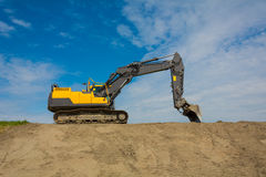 Large heavy duty excavator. On the skyline against a blue sky on top of earthworks in Zeeland Netherlands Stock Photography