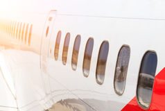 Large heavy modern passenger widebody airplane side close up detailed exterior view with exit door handle, passenger Royalty Free Stock Image