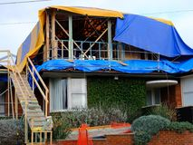 A Partly Completed Cape Cod Extension to a Sydney Suburban House, Australia. A large heavy weather protection tarpaulin stretched over the partly completed Stock Images