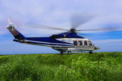 Large helicopter lands in the forest in the fog, Helicopter landing on the grass Stock Photo