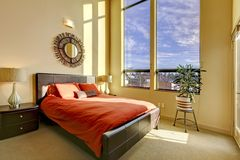Large high ceiling bedroom with red bed. Stock Photo