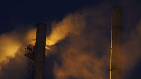 Large High Chimneys against Lit Smoke Clouds at Darkness stock video footage