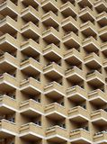 Large highrise modern apartment building with balconies. Large highrise modern apartment building with large number of repeating geometric balconies in stone Stock Photo