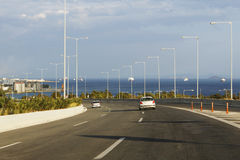 Large highway near sea in Greece. Riding on 3 lanes highway near the sea in Greece, surrounded by tall lighting poles stock photo