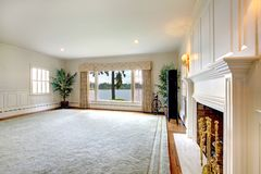 Large historical old living room interior with fireplace and lake view. stock photography