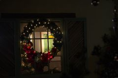 Large holiday wreath on home window at night. Glowing lights on holiday season pine wreath with red flowers hung in window of lit house royalty free stock image