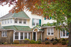 Large Home in Autumn. Large American mansion made of river stone and siding, a green roof. Fall colors surround the house, the trees leaves are red, orange Stock Photos