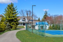 Large Home with Tennis Court in Lake Geneva, Wisconsin. A large home with Tennis Court in Lake Geneva, Wisconsin with pine trees and a tennis court in the front stock images